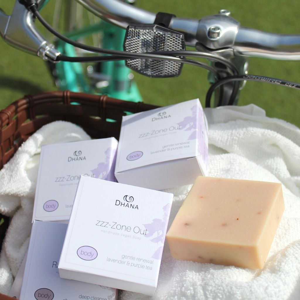 bike basket filled with soaps on a towel. Some are boxed and the label reads zzz-Zone Out Bath Bar, others are unwrapped showing a pink square bar.