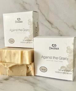 brown bars of soap with boxes on top and beside. The boxes read Against the Grain Shaving Soap from Dhana Selfcare. All on a Marble background.