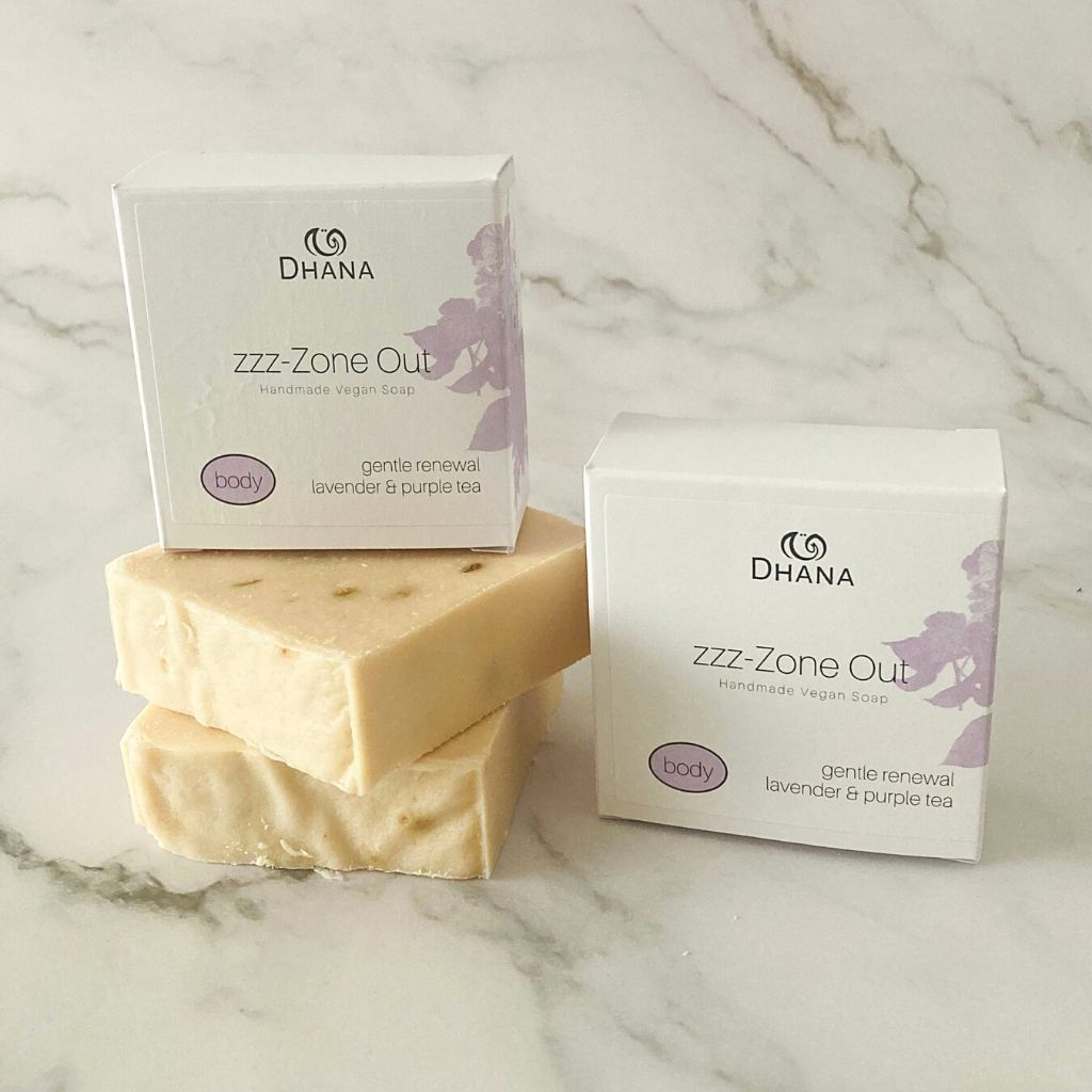 two peach coloured bars of soap stacked with its white box on top of it, and one beside. Both on a marble background.