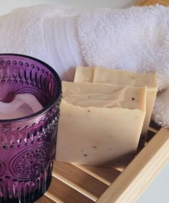 brown soap with a purple candle holder on a bamboo tray