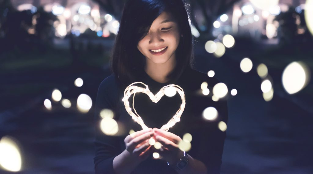 woman holding light of hearts