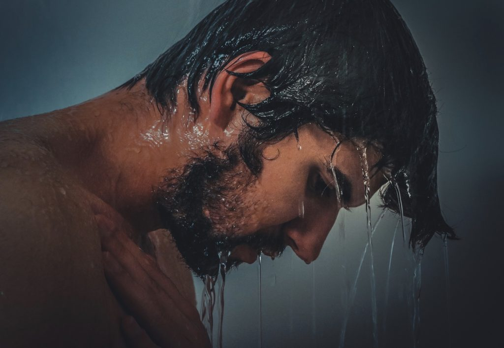 man with wet hair in shower