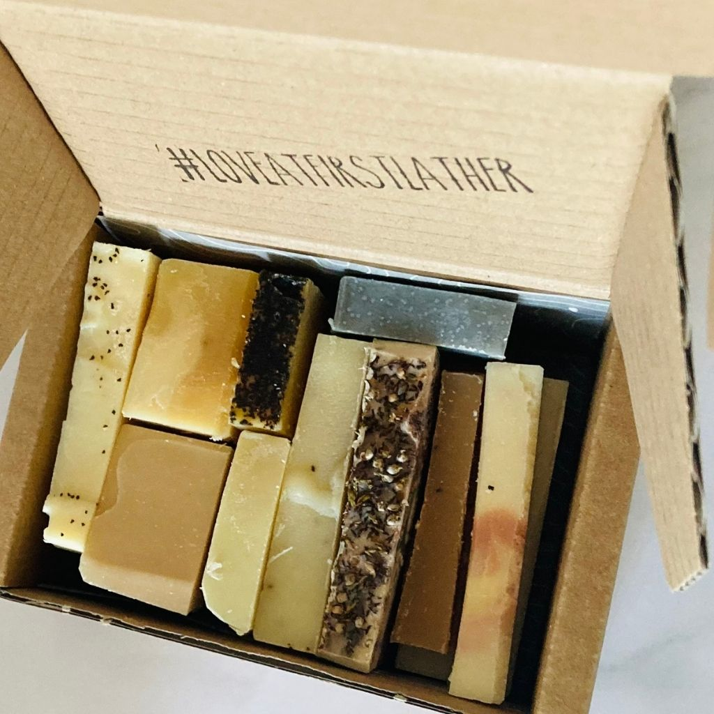 Soap slivers in a Kraft box. Miscellaneous colours and shapes of handmade soap packaged together.