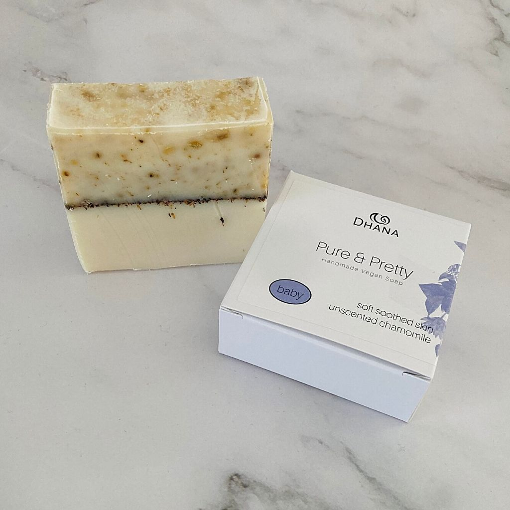 pure & pretty Dhana Soap bar RTSB01 has yellow variation on the top a black line across the middle and white on the bottom. P&P boxes are white and blue. The soap is unscented with ground chamomile flowers.