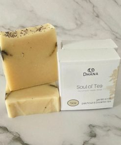 Two cream coloured soap bars speckled with black tea leaves beside a white box labelled Soul of Tea on a marble background
