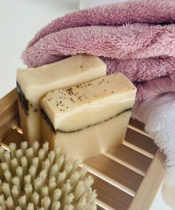 creamy beige soap bars with beads of tea leaves across each. Two sit lined up on a bath tray with a pink towel and a scrub brush.