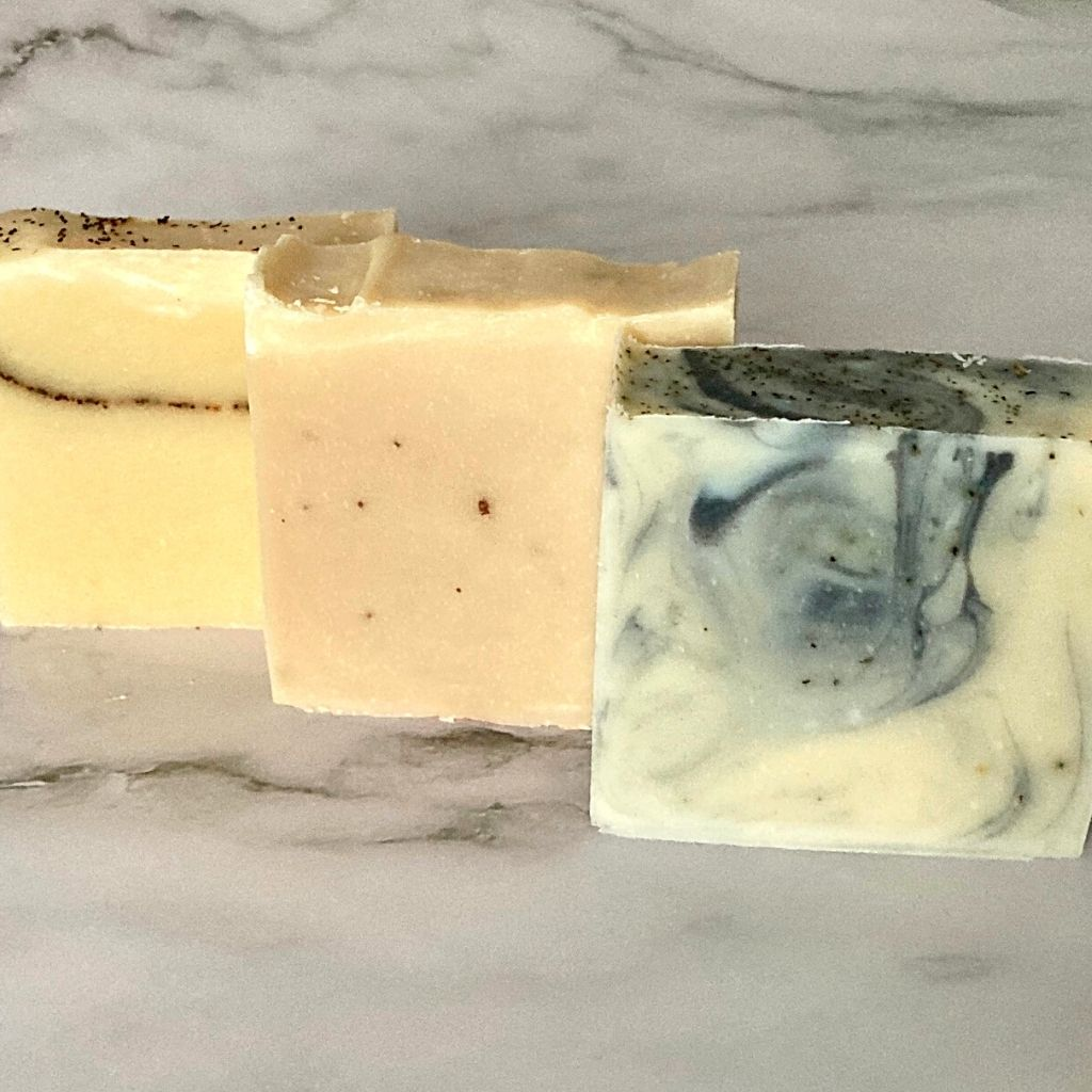 Three bars of soap in a row: a yellow one with a streak of tea leaves through it (soul of tea: English breakfast), a brown one with darker specks (called Against the Grain -rooibos spice), and a white and blue swirled bar (called Raise the Bar: earl grey)