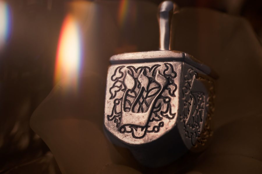 silver dreidel with a flame faded out in the background