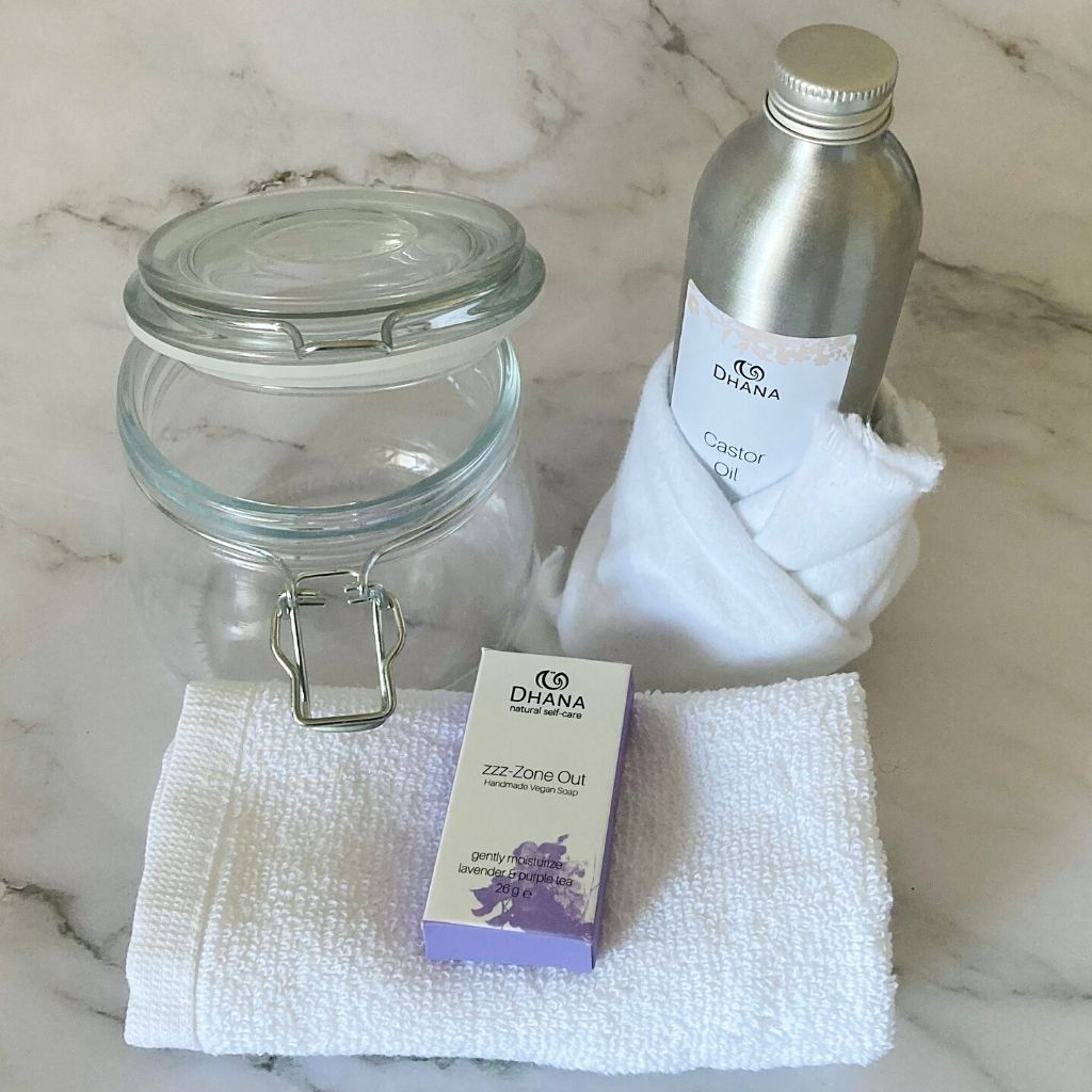 the contents of a castor oil packing kit from Dhana Selfcare. It is a sealable jar (left), and aluminum bottle of castor oil wrapped in a flannel. In the foreground is a facecloth of white cotton and a small purple bar of soap on top of it. All of this on a marble backdrop.