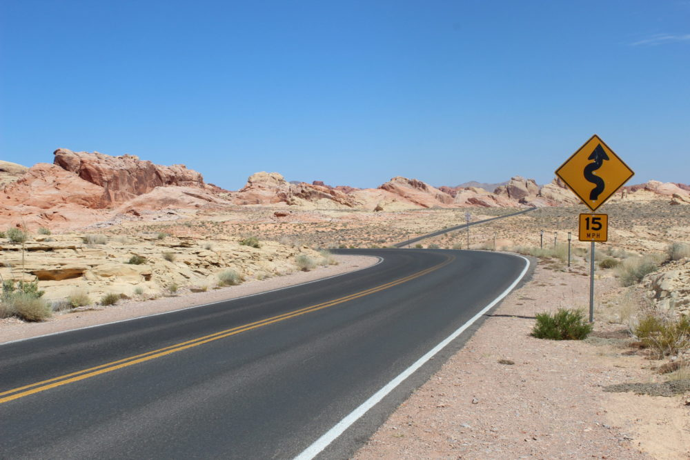 a windy road in the red desert. A road sign indicates wiggly road ahead. Picture taken in Valley of Fire State Park, Nevada, USA.