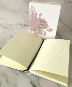 Journal with soft pink botanicals upright and one open with cream lined pages and black bookmark ribbon