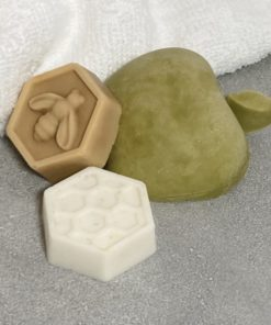 on a grey tile sits a green half apple shaped soap, flat side down and two honeycomb shaped soaps. One is white with honeycomb design and the other is brown like honey with a bee on it. These make up the Apple & Honey Rosh Hashanah Gift Collection.