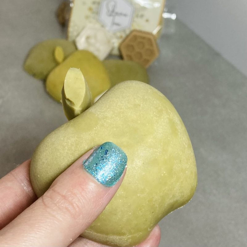a hand with turquoise finger nail holding a green apple soap with other honey and apple soaps in the background. They are out of focus. The held bar of soap is just wider than three fingers.