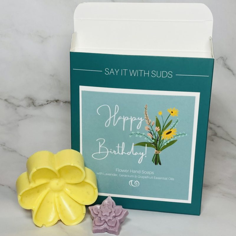 Happy Birthday Soap Box with a large yellow daisy soap and a tiny purple soap in front. Background is grey and white marble.